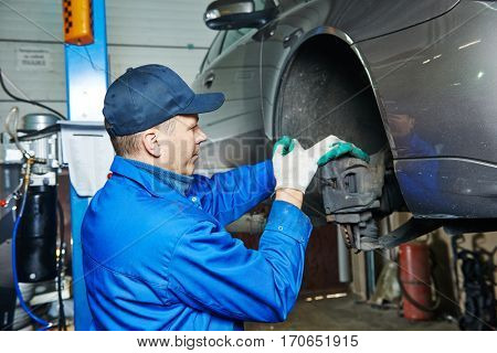 auto mechanic at car suspension repairing