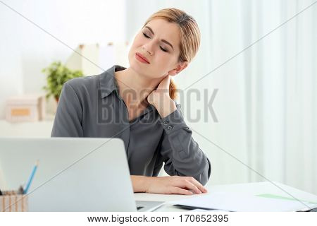 Beautiful woman suffering from neck pain in office