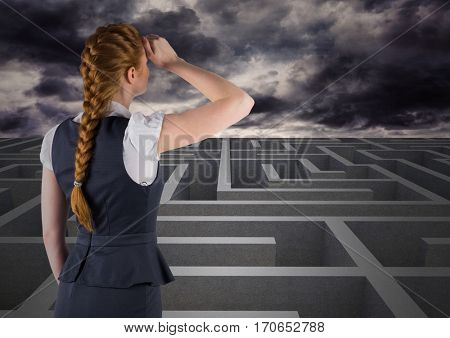 Rear view of businesswoman looking over digitally generated maze