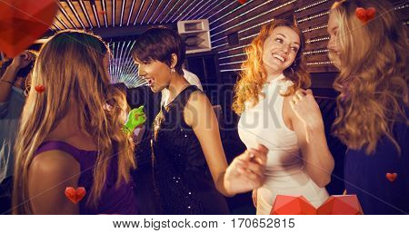 Group of smiling friends dancing on dance floor against hearts