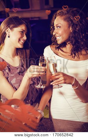 Cheerful young women toasting champagne flutes at bar counter against love heart pattern