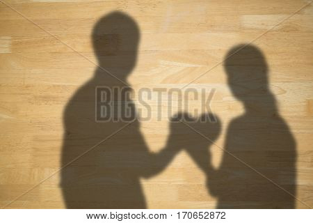Couple holding a red heart against bleached wooden planks background