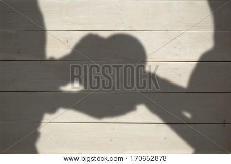 Couple holding heart shape gift against bleached wooden planks background