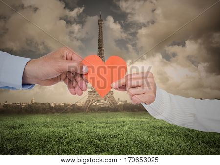 Close-up of couples hand holding heart against digitally generated eiffel tower at distance