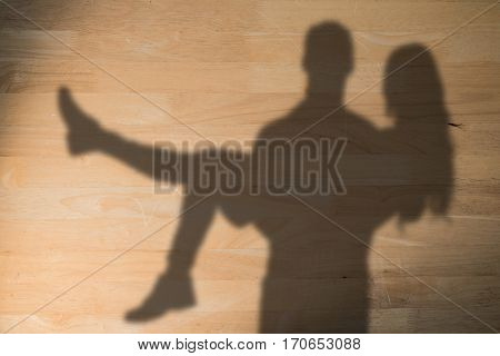 Portrait of boyfriend carrying girlfriend against bleached wooden planks background
