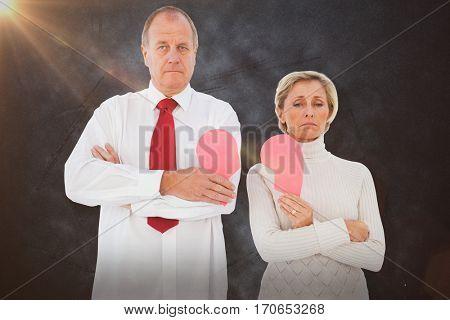 Older couple standing holding broken pink heart against grey