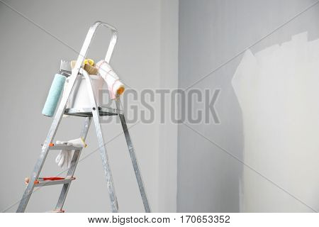 Ladder and set of tools for repair in empty room