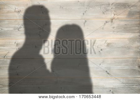 Portrait of couple hugging against bleached wooden planks background