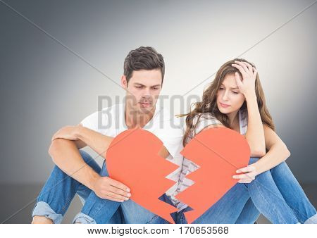 Sad couple holding broken hearts against grey background
