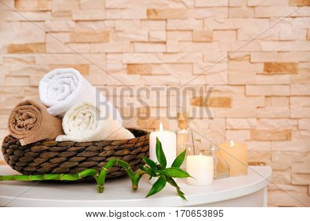 Spa composition with candles on light brick background
