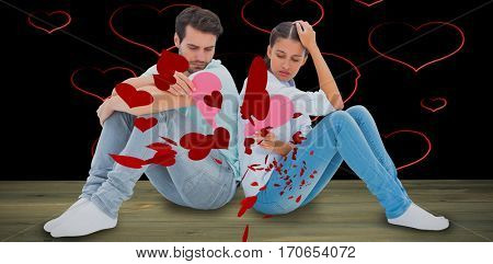 Sad couple sitting holding two halves of broken heart against red hearts floating