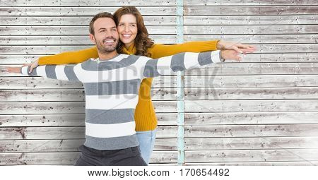 Happy couple standing with arms outstretched against wooden background