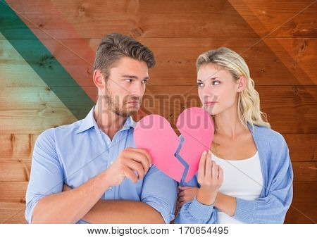 Sad couple looking each other while holding broken hearts against digital composite wooden background