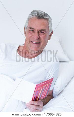 Portrait of happy of senior man holding birthday greeting card