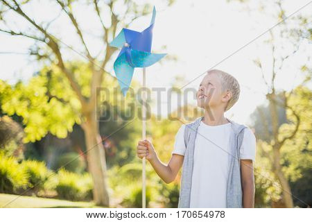 Boy holding a pinwheel and smiling in park