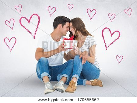 Romantic couple looking face to face and holding gift box against digitally generated heart background