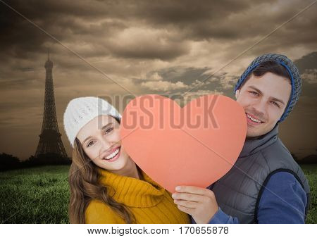 Portrait of romantic couple holding heart against digitally generated eifel tower background