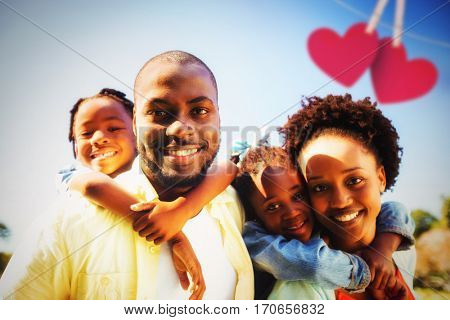 Hearts hanging on a line against couple posing together with their children at park