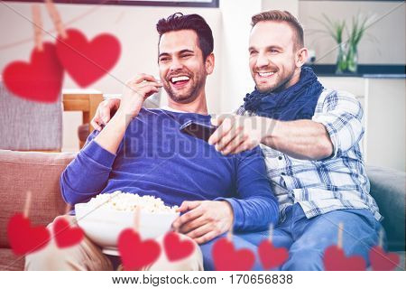 Hearts hanging on a line against gay couple watching television with pop corn