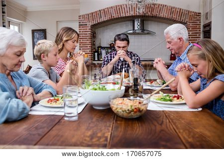 Multi-generation family praying before having meal at home
