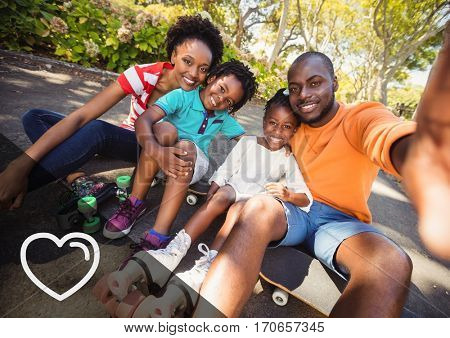 Portrait of happy family sitting on skate board in park