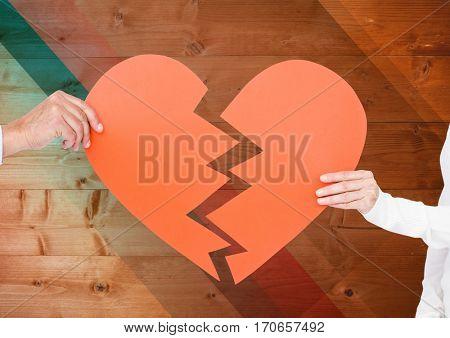 Hand of couple holding broken hearts against wooden background