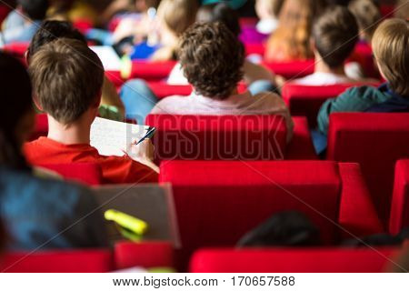 University students sitting in class, taking notes