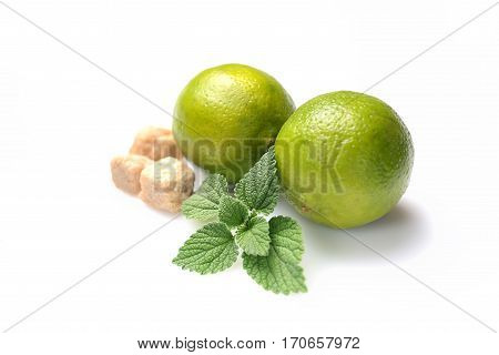 mint leaves, lime and brown sugar on a white background. Mojito cocktail ingredients