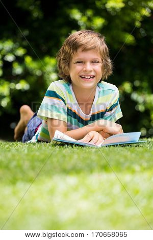 A little boy is lying down in the grass with a book