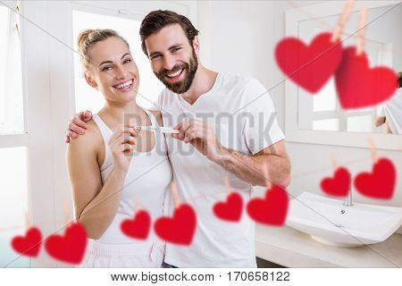 Portrait of happy couple holding pregnancy test in bathroom at home