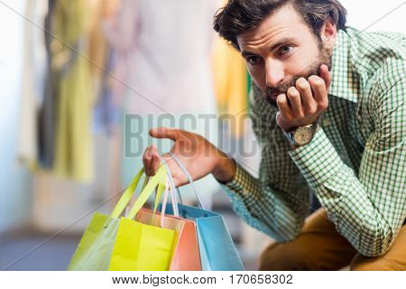 Bored man with shopping bags while woman by clothes rack in a shop