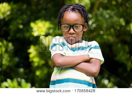 A kid posing with his arms crossed on a park