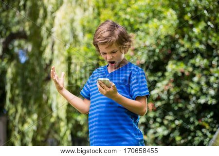 A little boy is angry with his mobile phone in a garden