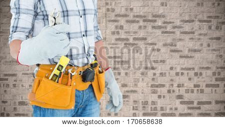Mid section of handyman holding pliers against brick wall