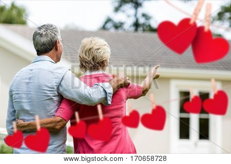 Composite image of red heart and senior couple pointing towards house
