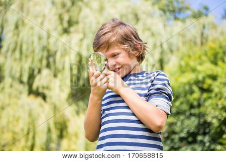 Portrait of happy boy looking a leaf with magnifying glasses on a park