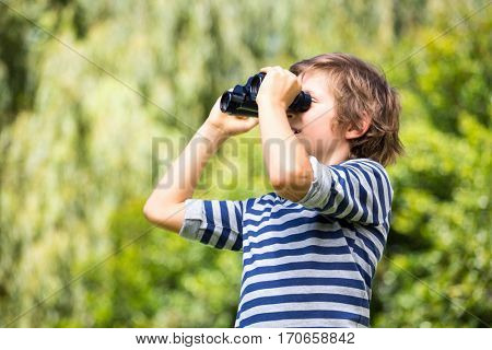 Portrait of cute boy looking something with binoculars on a park