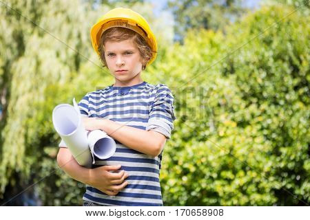 Portrait of serious boy pretending to be a worker on a park