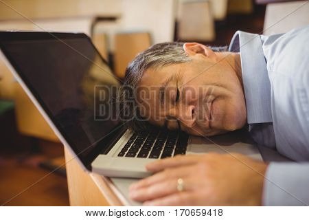 Professor sleeping on his laptop at desk in classroom