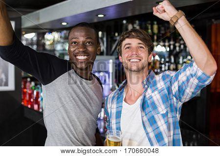 Happy friends watching sport in a bar