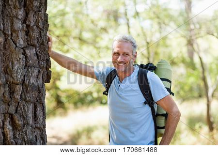 Hiker smiling and posing against a tree on the wood