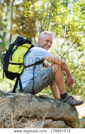 Hiker smiling and sitting on a rock on the wood