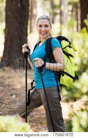 Portrait of a woman smiling and hiking on the wood