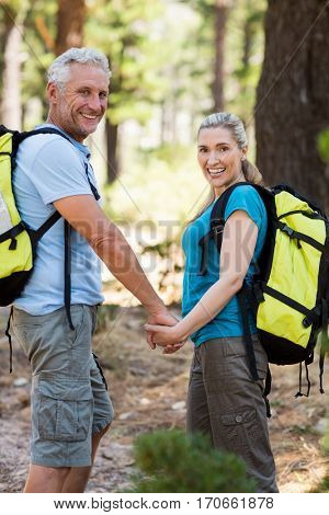 Couple smiling and holding hands each other on the wood