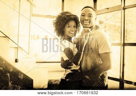 Grey background against portrait of happy couple embracing in their new home