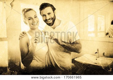 Grey background against portrait of happy couple checking pregnancy test