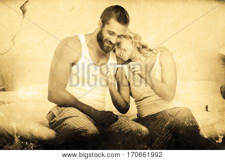 Grey background against happy couple looking at pregnancy test on bed