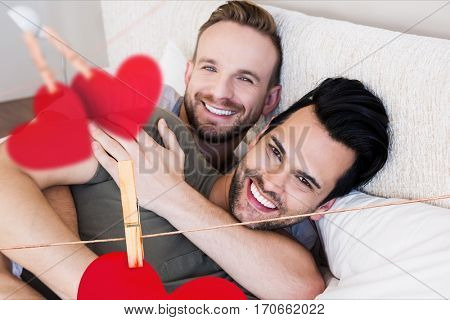 Composite image of red hanging hearts and homosexual couple embracing each other in bedroom at home
