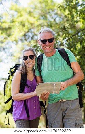 Couple smiling and holding a map on the wood