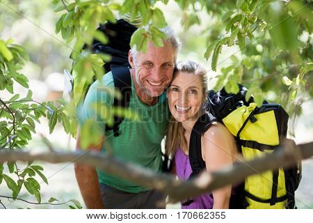 Couple smiling and posing during a hike on the wood